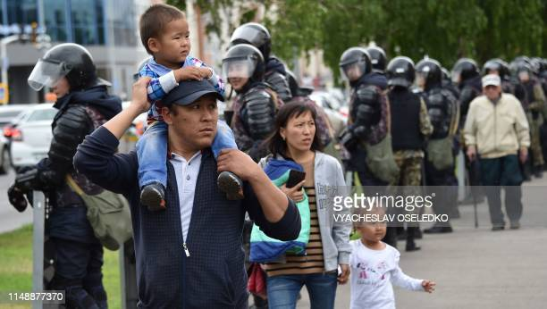 People walk as police line up along the street on June 10 2019 in NurSultan a day after Kazakhstan's presidential elections Kazakhstan elected the...