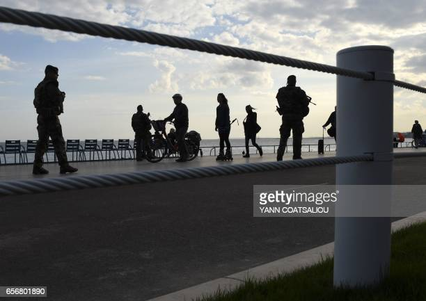 People walk as soldiers stand guard on March 22 2017 on the seafront Promenade des Anglais in Nice southeastern France where bollards and fences are...