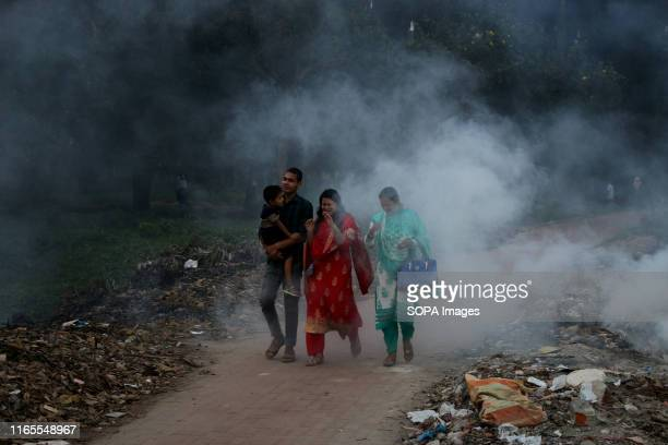 People walk as the garbage burns beside a street at a park in Dhaka Dhaka was named the second most polluted capital city in the world in 2018...