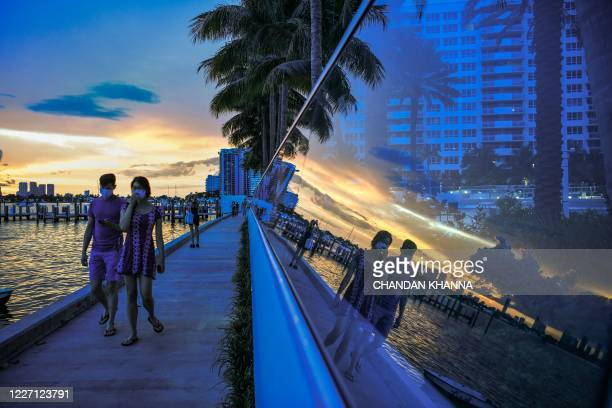 People walk as the sun sets in the background in South Bay, Miami Beach, Florida on July 14 amid the coronavirus pandemic. - The US state of Florida...