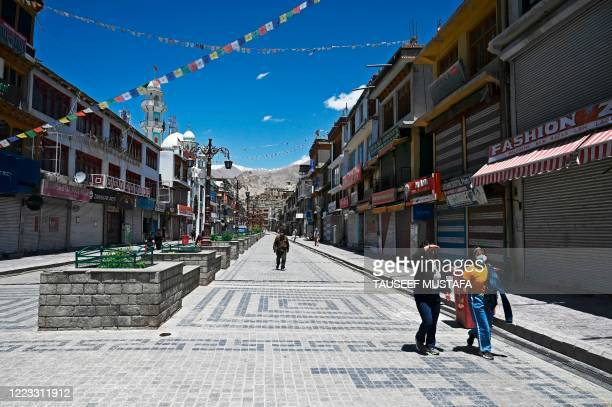 People walk at a closed market amid concerns over the spread of the COVID-19 coronavirus in Leh, the joint capital of the union territory of Ladakh,...