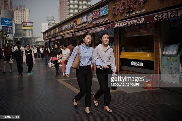 People walk at a shopping mall complex in Zhengzhou on October 19 2016 China's growth slipped to a sevenyear low of 66 percent in the third quarter...