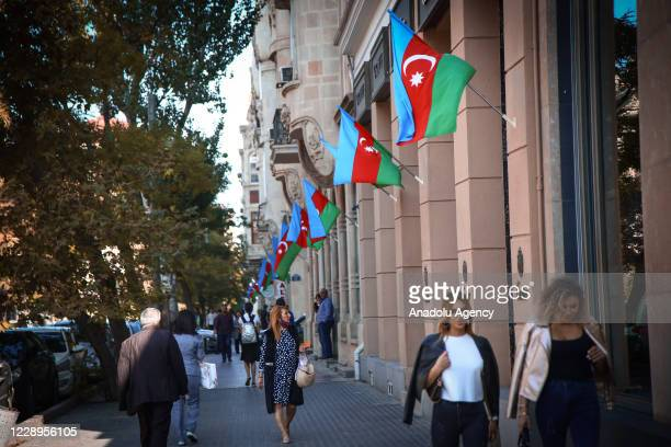 People walk at a street as flags of Azerbaijan are hanged on buildings and streets in Baku Azerbaijan on October 08 2020