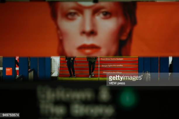 People walk at a subway station while images of David Bowie are displayed as art installations on April 20 2018 in New York NY A Bowie exhibition...