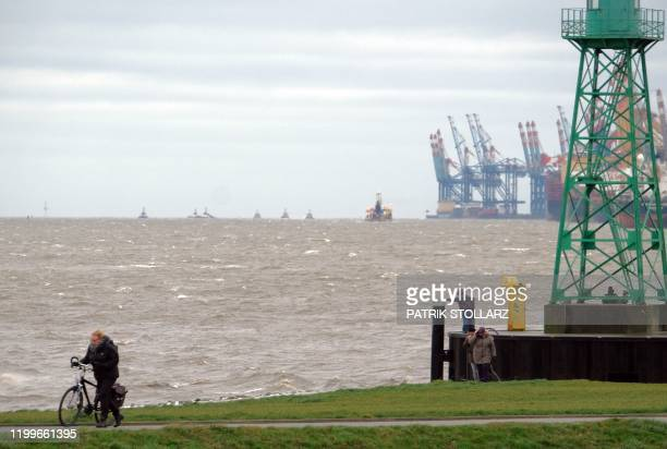 People walk at bank of the North Sea in Bremerhaven northern Germany on Febuary 9 2020 The storm named Sabine is estimated arriving along the north...