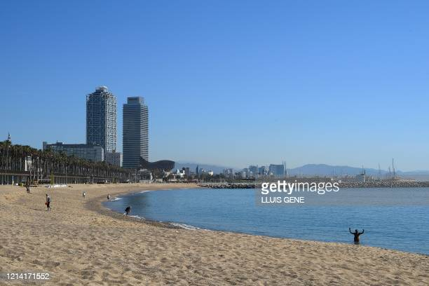 People walk at Barceloneta beach in Barcelona on May 20, 2020 during the hours reserved for the elderly, amid the national lockdown to prevent the...
