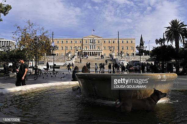 People walk at central Athens Syntagma square in front of the Parliament in Athens on November 8 2011 Greece inched towards a deal on a new premier...