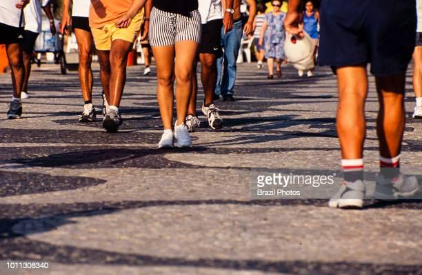 People walk at Copacabana beach sidewalk in the morning Calcadao de Copacabana Rio de Janeiro Brazil The promenade is a pavement landscape in large...