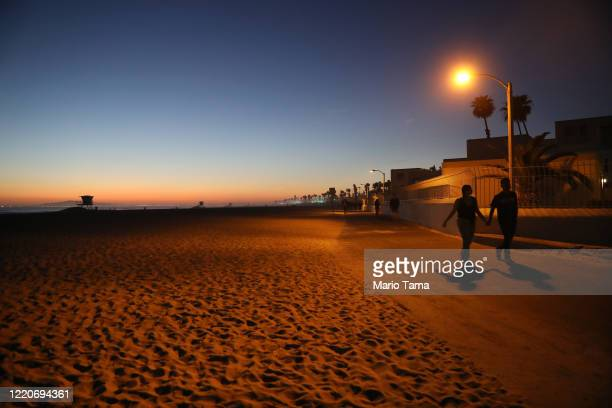 People walk at dusk on Huntington Beach which remains open amid the coronavirus pandemic on April 23 2020 in Huntington Beach California Neighboring...