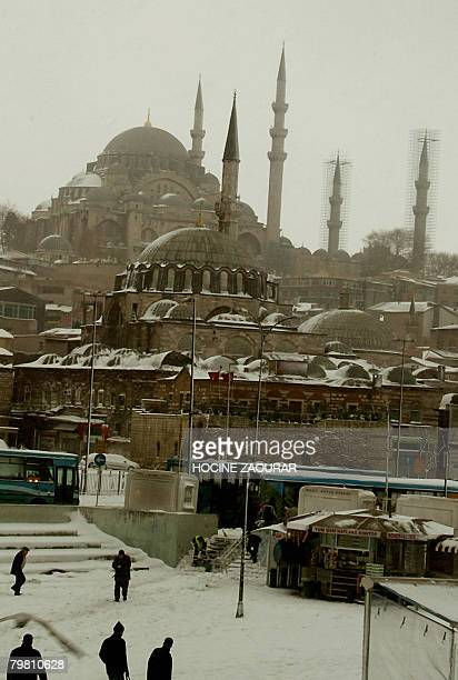People walk at Eminonu district in Istanbul as the Suleymaniye mosque appears in the background following a snow storm on February 17 2007 AFP...