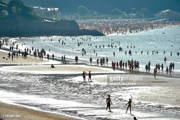 TOPSHOT People walk at La Concha beach in the northern Spanish city of San Sebastian on June 26 2019 at the start of a heatwave tipped to break...