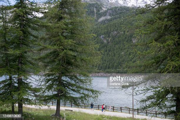 People walk at Lake Ceresole Reale inside the Gran Paradiso national park on June 14, 2020 in Ceresole Reale near Turin, Italy. The Gran Paradiso...