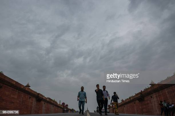 People walk at Rashtrapati Bhavan as dark clouds hover over the city on June 26 2018 in New Delhi India Temperature reduced to 27 degrees Celsius as...