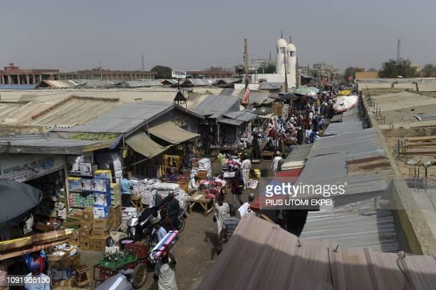 TOPSHOT People walk at Sabon Gari Market in Kano on January 30 2019 Nigerian President Mohammadu Buhari has flag off campaign in Kano the commercial...