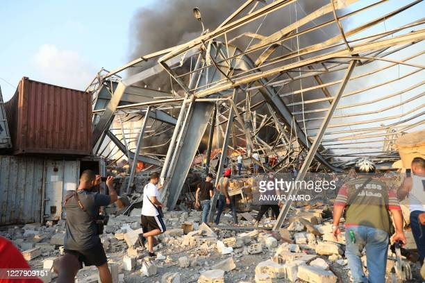 TOPSHOT People walk at scene of an explosion in Beirut on August 4 2020 A large explosion rocked the Lebanese capital Beirut today an AFP...