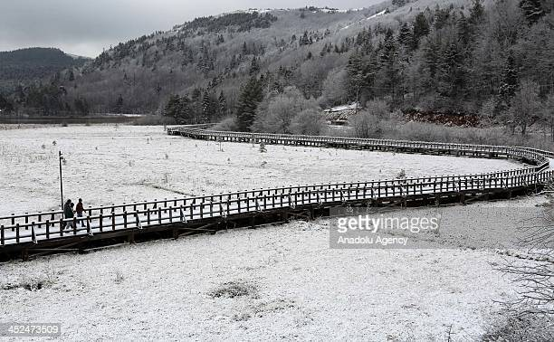 People walk at snow covered Abant Nature Park on November 29 2013 in Bolu Turkey