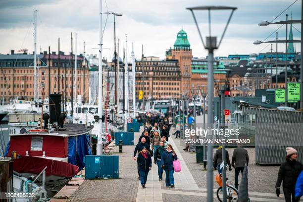 People walk at Strandvagen in Stockholm on March 28 during the the new coronavirus COVID19 pandemic Sweden which has stayed open for business with a...