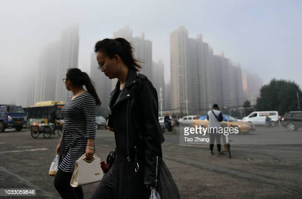 People walk at the Changjiang street during dense fog enveloping Harbin on September 14 2018 in Harbin China The meteorological department issued a...