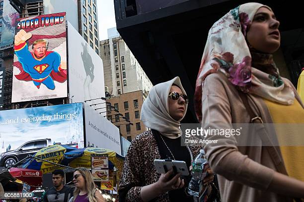 People walk at the corner of 47th Street and 7th Avenue as an animated digital billboard supporting Donald Trump plays behind them in Times Square...