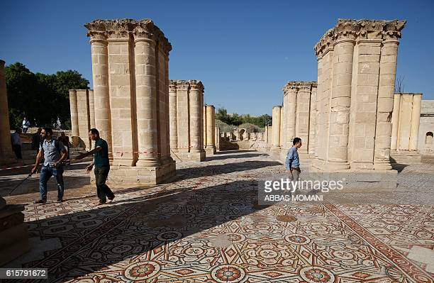 People walk at the Hisham's Palace archaeological site located five kilometres north of the West Bank city of Jericho on October 20 after the mosaic...