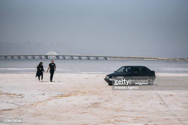 People walk at the Lake of Urmia in the northwest of Iran, which had been shrinking in one of the worst ecological disasters of the past 25 years,...