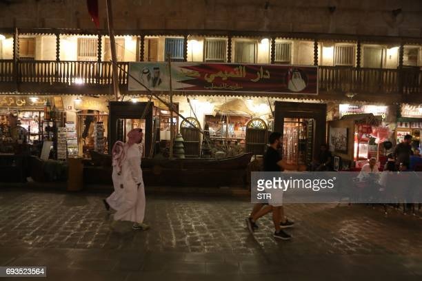 People walk at the popular Souq Waqif market in the Qatari capital Doha on June 7 2017 Saudi Arabia Egypt the UAE and Bahrain announced on June 5...