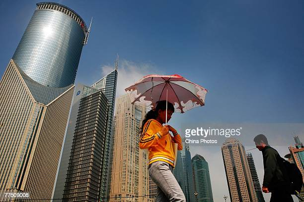 People walk at theat the Lujiazui Financial District on October 26 2007 in Shanghai China Chinese President Hu Jintao said during the 17th National...