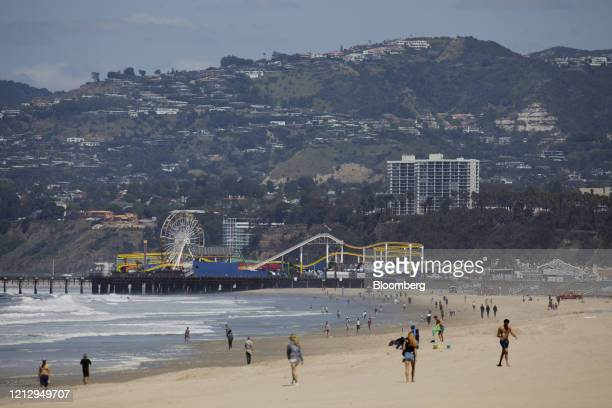 People walk at Venice Beach in front of the Santa Monica Pier in Los Angeles, California, U.S., on Wednesday, May 13, 2020. Los Angeles County...