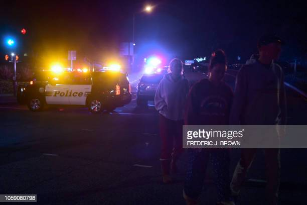 People walk away from the scene as it unfurls at the intersection of US 101 freeway and the Moorpark Rad exit as police vehicles close off the area...