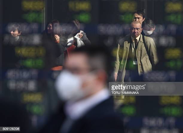 People walk before an electric quotation board flashing share prices of the Tokyo Stock Exchange in front of a securities company in Tokyo on...