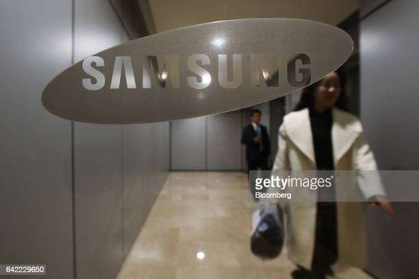 People walk behind Samsung Electronics Co signage at the company's Seocho office building in Seoul South Korea on Friday Feb 17 2017 Samsung Group's...