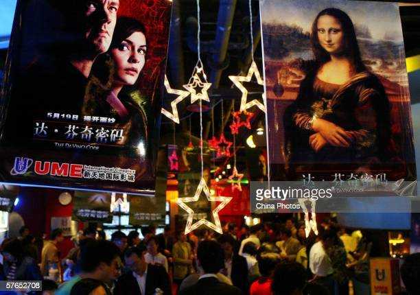 People walk below posters of movie 'The Da Vinci Code' at the Xintiandi entertainment center on May 18 2006 in Shanghai China 'The Da Vinci Code'...