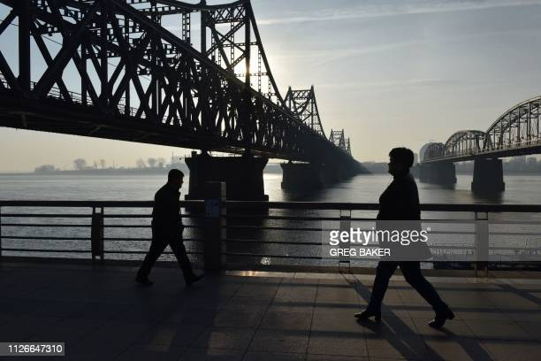 People walk below the Friendship Bridge , which spans the Yalu River between China and North Korea, in the Chinese border city of Dandong, in China's...