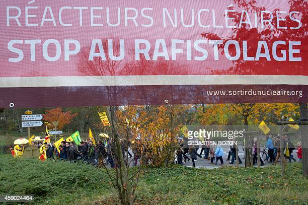 People walk beneath a banner reading 'Nuclear reactors stop to makeshift repair'' during a demonstration against antinuclear power on November 15...