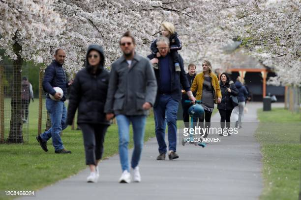 People walk beneath blossoming trees as they take their daily exercise allowance in Battersea Park in London on March 28 as life in Britain continues...