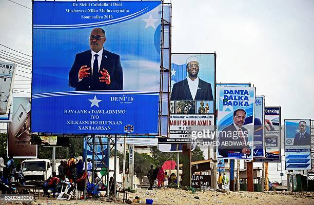 People walk beneath campaign posters of the forthcoming Somali presidential elections in Mogadishu Somalia on December 20 2016 The new Federal...