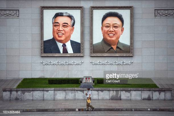 People walk beneath huge pictures of Kim Ilsung and Kim Jongil displayed from the Parade Reviewing Stand in Kim Ilsung Square on August 23 2018 in...