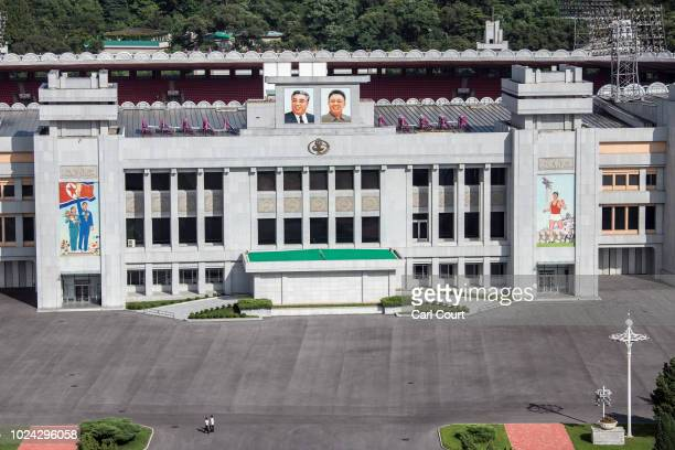 People walk beneath pictures of Kim Il-sung and Kim Jong-il displayed on the Kim Il-sung Stadium, on August 21, 2018 in Pyongyang, North Korea....
