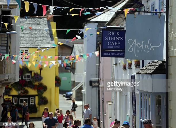 People walk beneath signs outside two business run by celebrity chef Rick Stein in a street near the harbour on August 19 2013 in Padstow England...