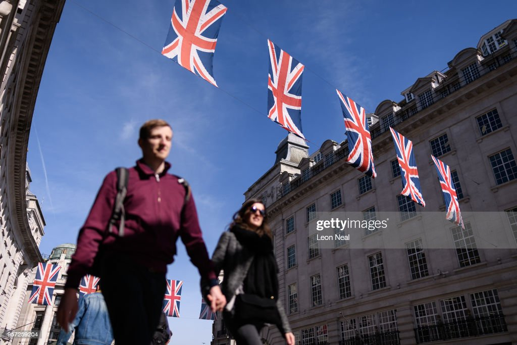 People walk beneath the Union Flags on Regent Street, displayed ahead of the wedding of Prince Harry and Meghan Markle, on May 11, 2018 in London, England.