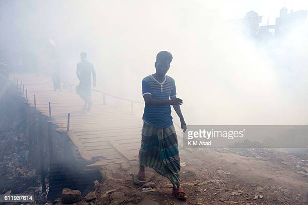 MOHAMMADPUR DHAKA BANGLADESH People walk beside in the waste burning dumps area producing smoke and toxic pollution at Mohammadpur According to the...