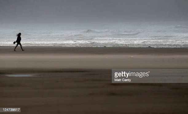 People walk beside the rough seas at Rhossili Bay in the Gower near Swansea on September 12 2011 in Wales Parts of the country are to be hit by...