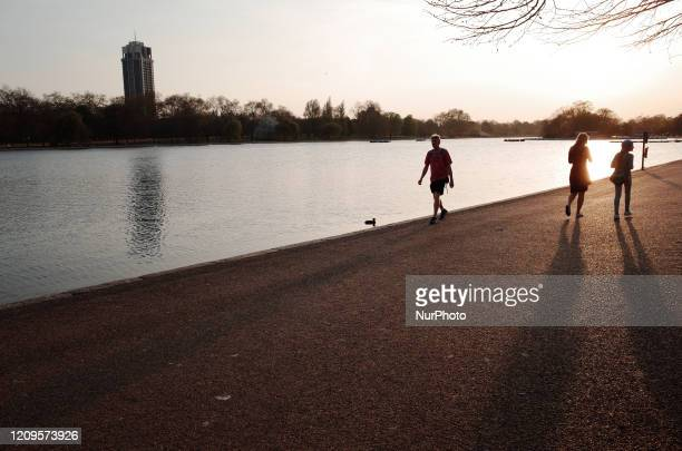 People walk beside the Serpentine lake in Hyde Park at sunset in London, England, on April 9, 2020. As Britain begins what is forecast to be a warm...