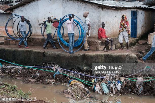 People walk besides the Nairobi River during the community cleanup event supported by UN Environment at Kibera slum in Nairobi Kenya on Africa day...