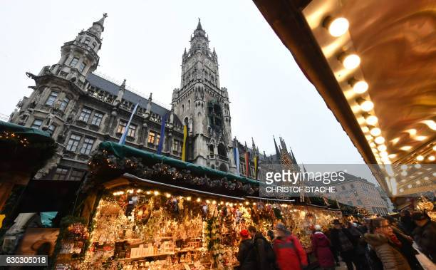 People walk between booths of the Christmas market in front of the city hall at the Marienplatz in Munich southern Germany on December 20 one day...