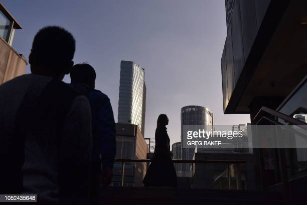 TOPSHOT People walk between buildings at a shopping mall in Beijing on October 18 2018 Asian markets resumed their downtrend on October 18 as...