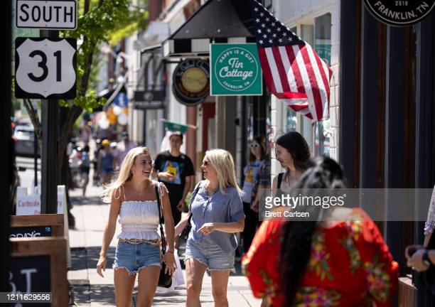 People walk between shops and restaurants that have reopened this week following loosening of non essential business restrictions on May 2 2020 in...