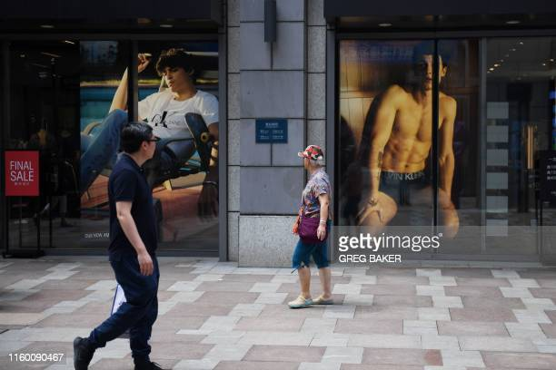 People walk between stores in a shopping mall in Beijing on August 7 2019 China's move to devalue its currency could prove to be a doubleedged sword...