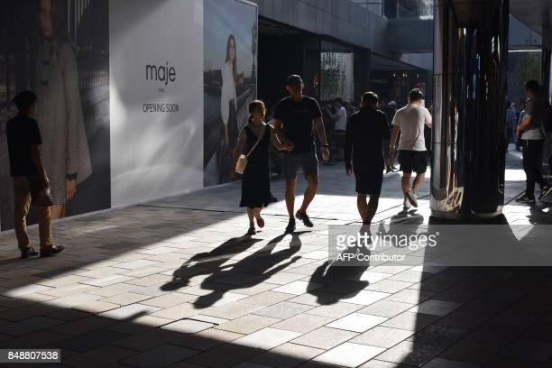 People walk between stores in a shopping mall in Beijing on September 18 2017 / AFP PHOTO / GREG BAKER