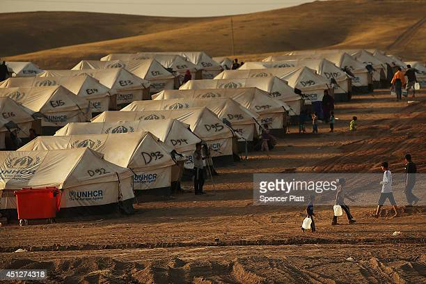 People walk between tents at a displacement camp for those caughtup in the fighting in and around the city of Mosul on June 26 2014 in Khazair Iraq...